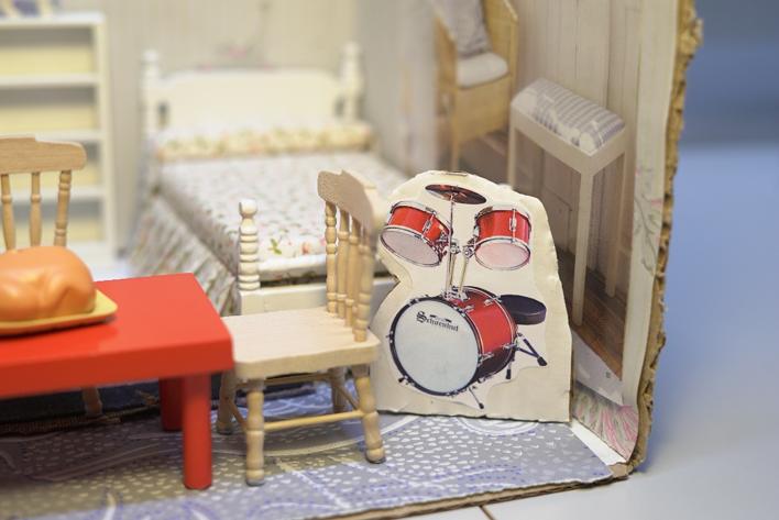 Detalj från ett papphus med dockhusmöbler och bild på ett trumset.