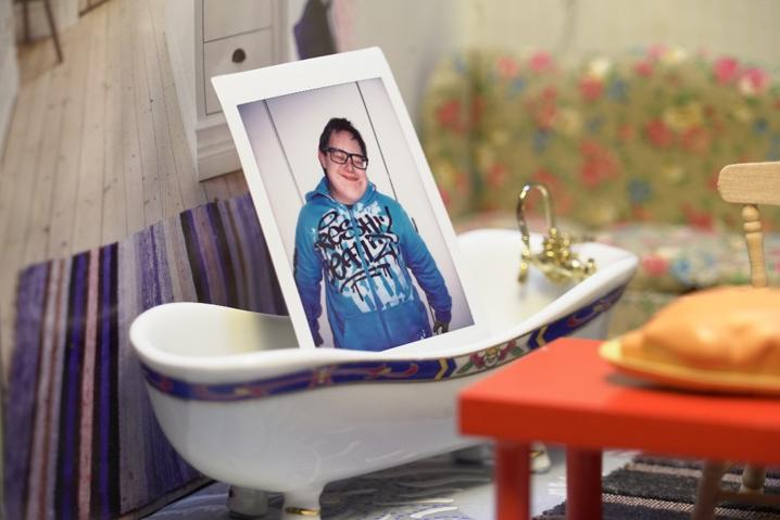Ett kort på en människa i ett dockhusbadkar i ett papphus.