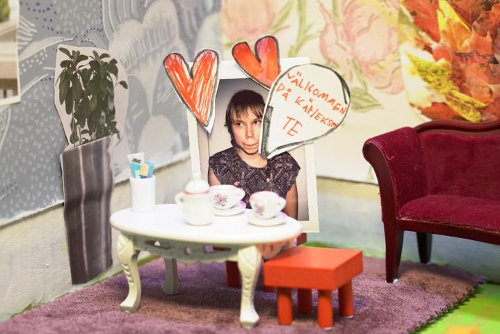 Vid ett tebord i ett papphus finns kort på en kvinna som säger Välkommen på kärlekste.